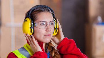 vrouw draagt gehoorbescherming op het werk